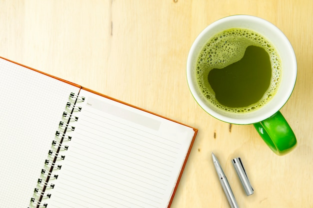 Abra o caderno e a pena com greentea no fundo de madeira. vista superior, conceito plana lay.
