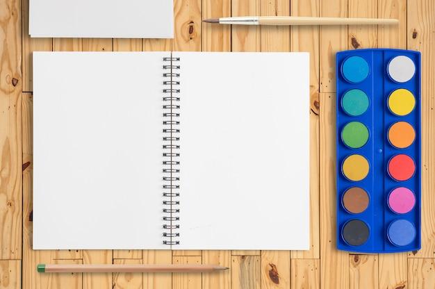 Abra o caderno e aquarela pintura a aguarela paleta na tabela de madeira