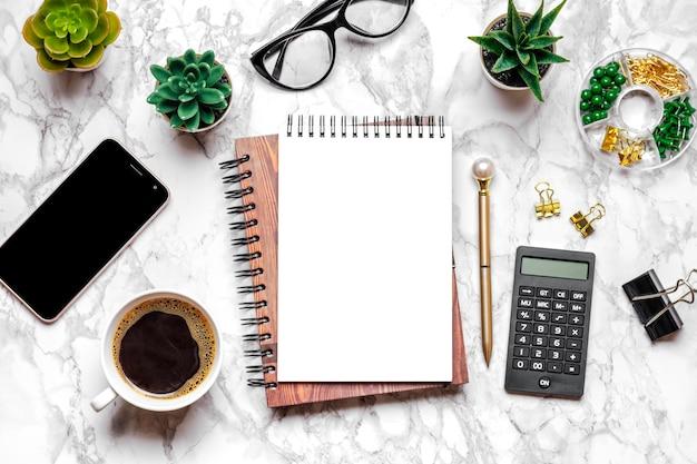 Abra o caderno em branco, copos, xícara de café, caneta, smartphone, suculentas na mesa de mármore vista superior