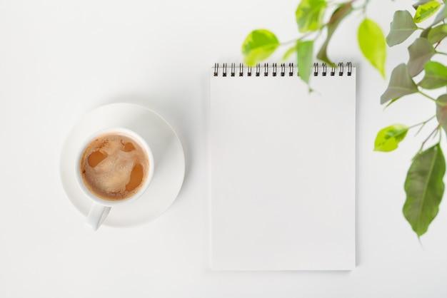 Abra o caderno em branco em uma espiral, xícara de porcelana branca com café e folhas de uma planta de casa.