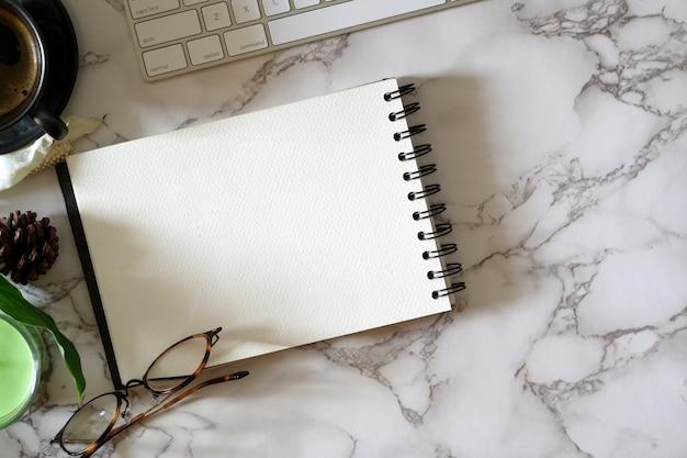 Abra o caderno em branco na mesa de tampo de mármore com material de escritório
