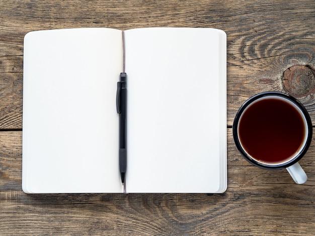 Abra o caderno em uma mola com um papel branco para notas e desenho perto de um lápis e um copo