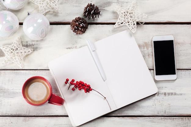 Abra o caderno na mesa de madeira com um telefone e decorações de natal