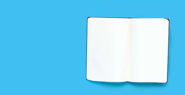 Abra o caderno sobre fundo azul. vista do topo