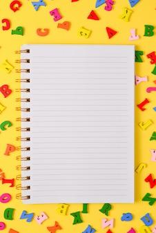 Abra o caderno vazio e letras coloridas em um fundo amarelo. vista do topo. espaço para texto ou desenho.