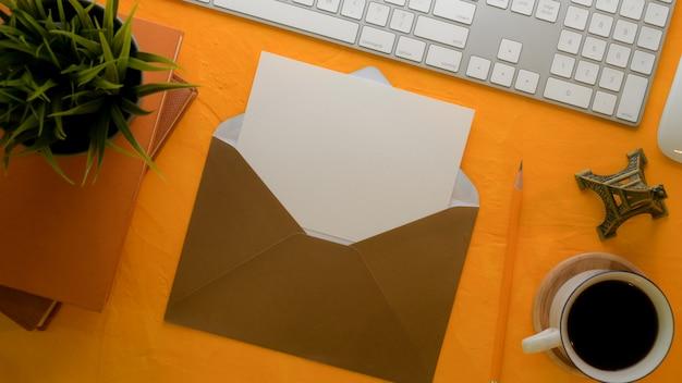Abra o cartão com envelope marrom na mesa de trabalho criativa com material de escritório e decorações