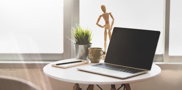 Abra o computador portátil na mesa de madeira branca