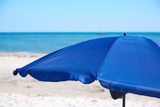 Abra o guarda-chuva de praia têxtil azul em uma praia arenosa