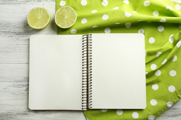 Abra o guardanapo do livro de receitas na mesa de madeira