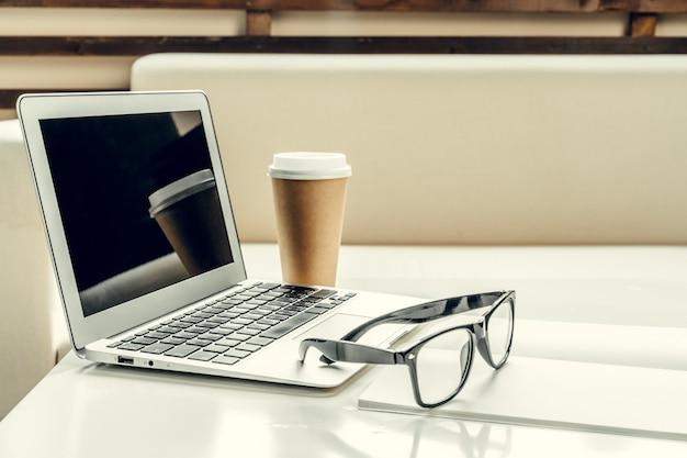 Abra o laptop na mesa perto do sofá, interior de casa.