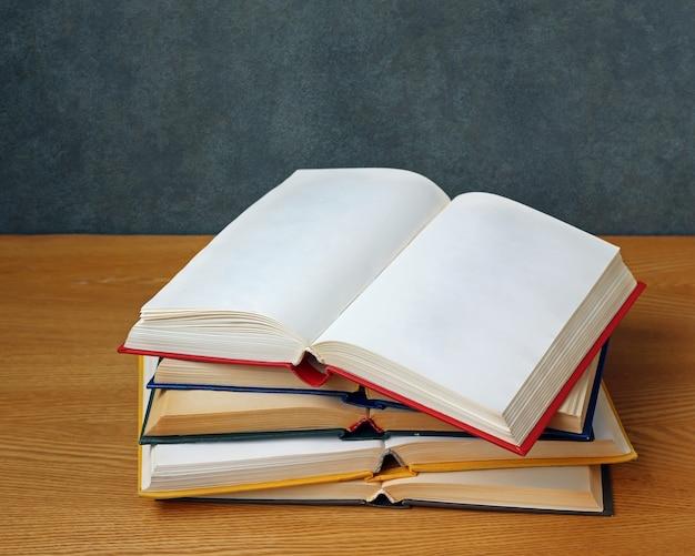 Abra o livro com páginas em branco sobre uma pilha de outros livros sobre a mesa.