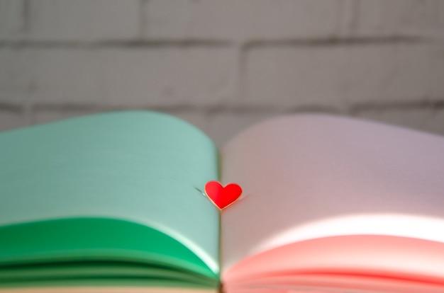 Abra o livro com páginas verdes e rosa claras e um coração de vidro vermelho no centro. cartão delicado, cores pastel