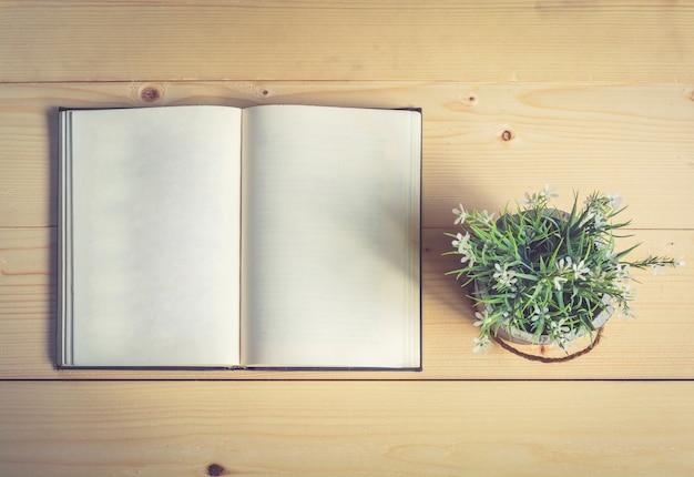 Abra o livro com um vaso de flores na mesa de madeira
