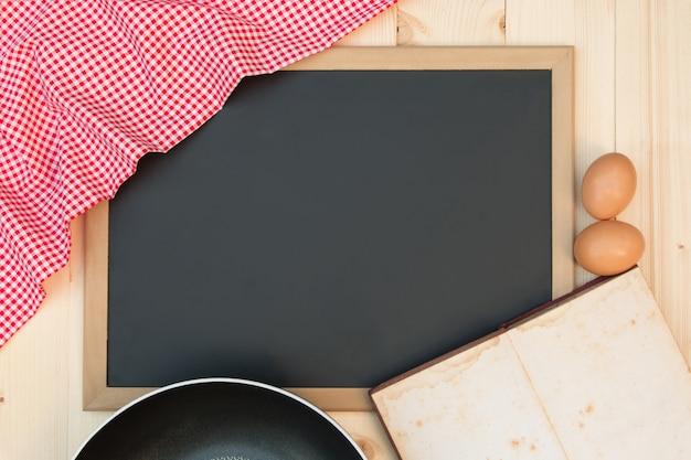 Abra o livro de receitas em um quadro negro com uma toalha de mesa quadriculada vermelha