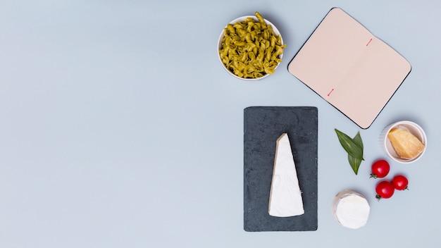 Abra o livro em branco e massas alimentícias não cozidas com ingrediente sobre pano de fundo cinzento