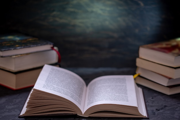 Abra o livro em uma pilha de livros sobre uma mesa. educação e leitura de livros de papel