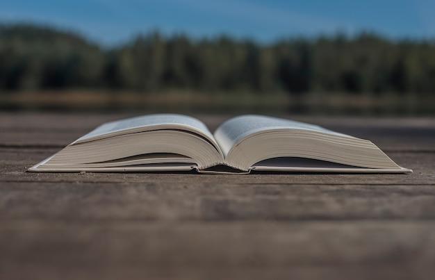 Abra o livro moderno na mesa de madeira, com espaço de cópia para o texto e a paisagem da natureza no conceito de fundo.
