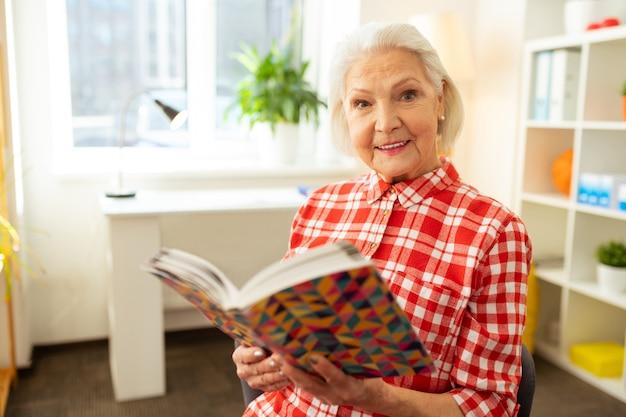 Abra o livro. mulher de cabelos grisalhos positiva segurando um livro enquanto o lê