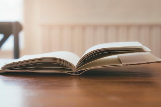 Abra o livro na mesa de madeira.