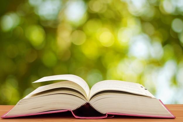 Abra o livro na mesa na frente do fundo verde bokeh
