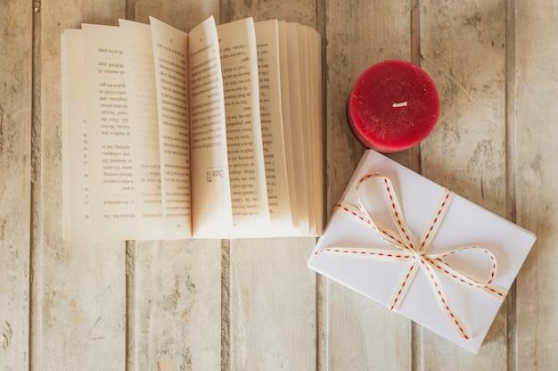 Abra o livro, vela vermelha e caixa de presente
