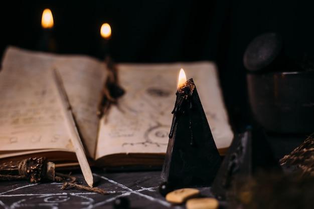 Abra o livro velho com feitiços, runas, velas negras na mesa de bruxa. conceito oculto, esotérico, adivinhação e wicca. cena do dia das bruxas