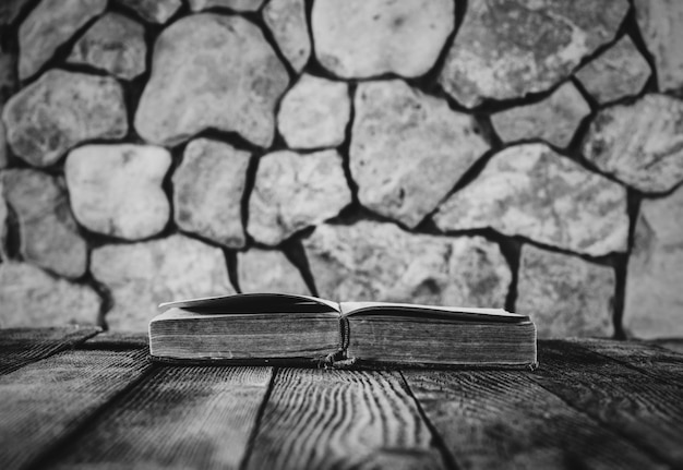 Abra o livro velho na mesa de madeira velha em uma das paredes de pedra. foco seletivo, preto e branco. com espaço para o seu texto