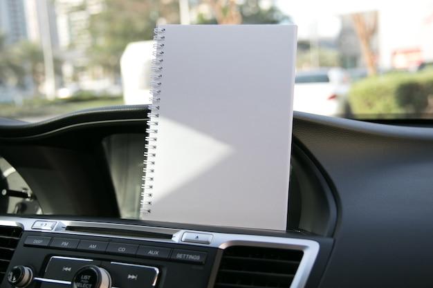 Abra o notebook com páginas em branco, vazias e transparentes no painel de controle do carro