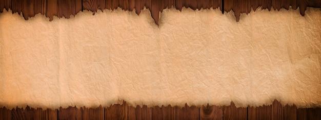 Abra o pergaminho antigo em uma mesa de madeira, papel panorâmico fundo