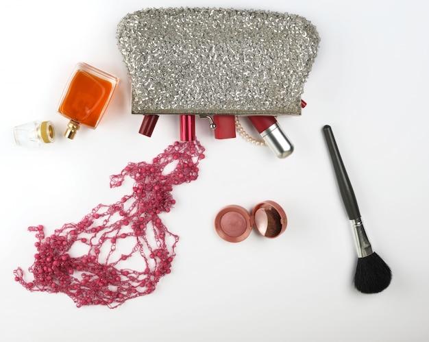 Abra o saco cosmético prateado e os cosméticos e perfumes femininos, batom vermelho
