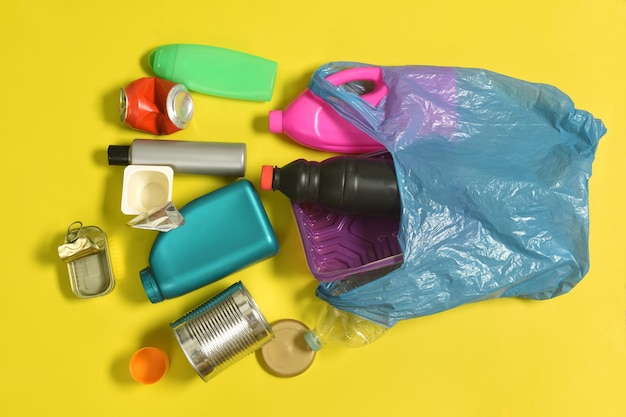 Abra o saco de lixo com garrafas de plástico e lata espalhada