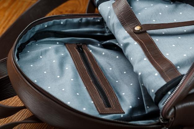 Abra o saco vazio feito de couro genuíno artesanal com elementos de fechaduras em uma mesa de madeira.
