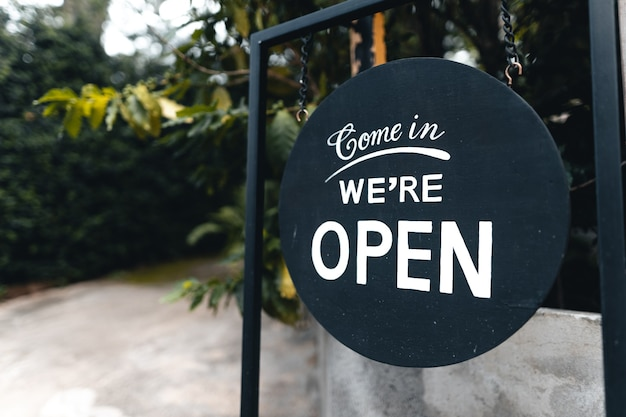 Abra o sinal largo pendurado na porta de madeira do café.