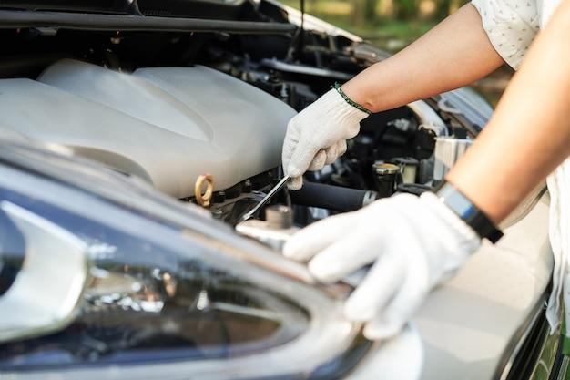 Abra o sistema do motor mecânico do capô para verificar e reparar o acidente de carro danificado.