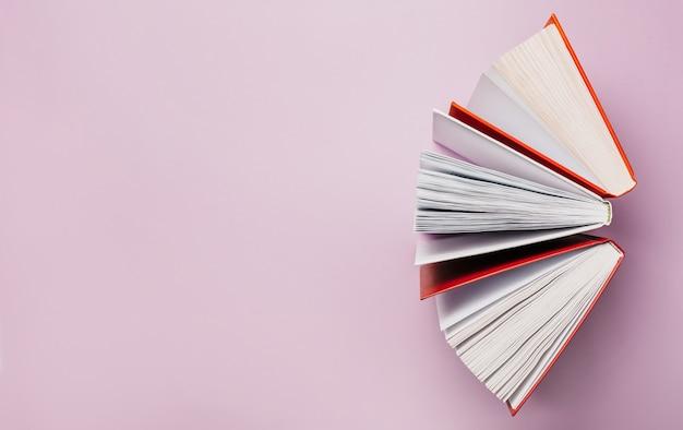Abra os livros em uma superfície rosa