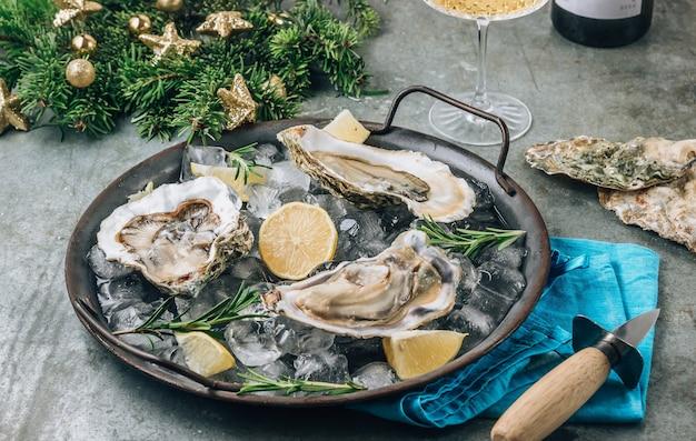Abra ostras crus com limão e alecrim. frutos do mar frescos em uma bandeja de metal. conceito de natal