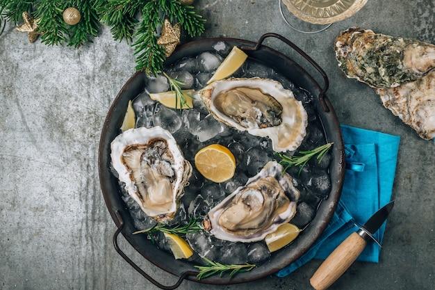 Abra ostras crus com limão e alecrim. frutos do mar frescos em uma bandeja de metal vista superior. conceito de natal