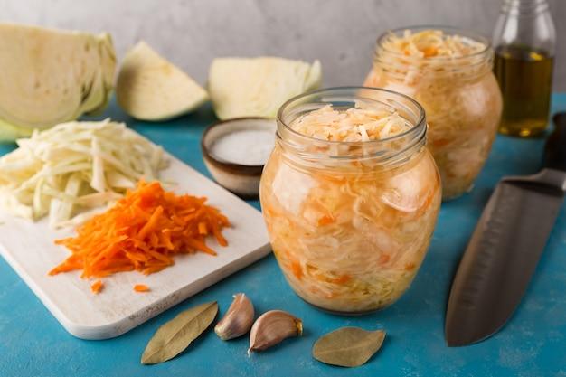 Abra potes de chucrute em fundo azul com fatias de repolho fresco e sal de cenoura