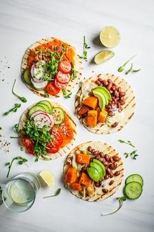 Abra tortilhas vegetarianas com batata doce, feijão, abacate, tomate, abóbora e brotos em fundo branco, configuração plana, cópia espaço. conceito de comida vegetariana saudável.