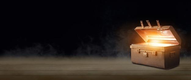 Abra um baú de tesouro antigo que irradiava luz na escuridão.