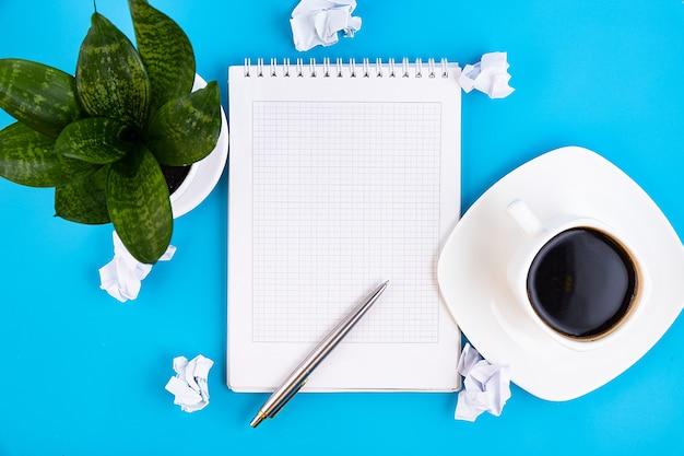 Abra um caderno branco em branco com caneta e xícara de café e papéis amassados em uma mesa azul. conceito de negócios