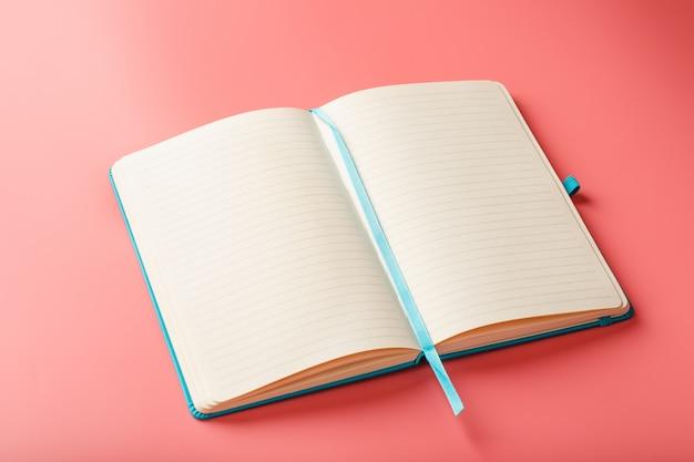 Abra um laptop com páginas em branco em um fundo rosa. vista superior, espaço de cópia