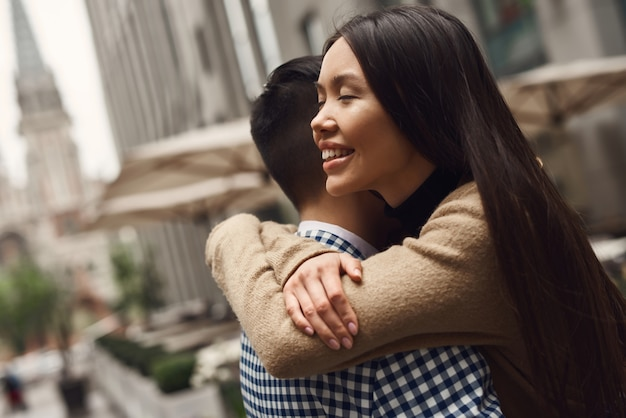 Abraçando a menina asiática da paisagem urbana fechou os olhos.