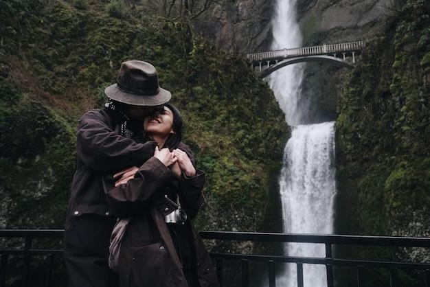 Abraçando casal asiático está diante de uma bela cachoeira nas montanhas