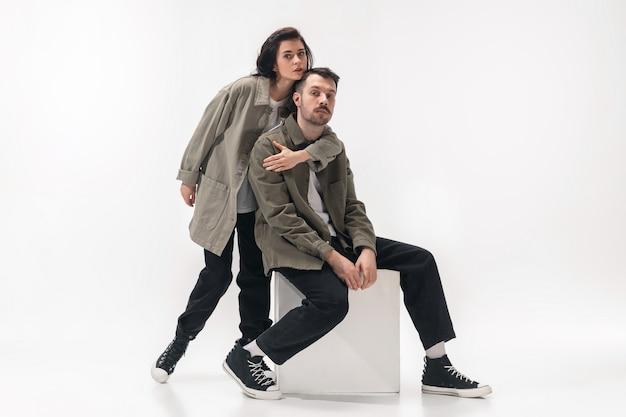 Abraçando. casal na moda moderno isolado no fundo branco do estúdio. mulher caucasiana e homem posando com roupas elegantes mínimas básicas. conceito de relações, moda, beleza, amor. copyspace.