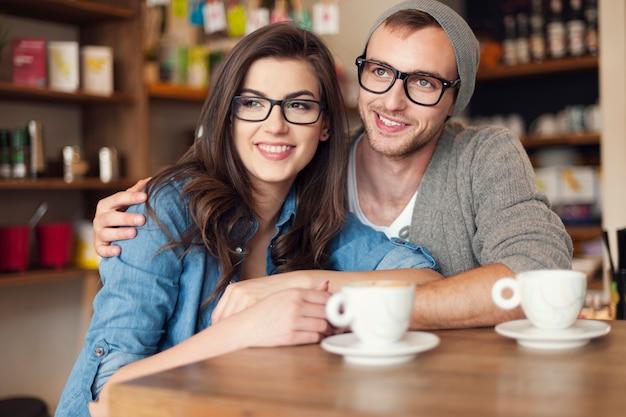 Abraçando casal passando juntos em um café