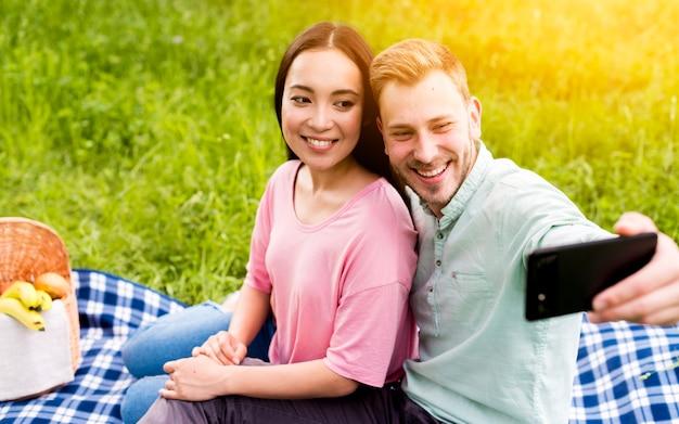 Abraçando casal tendo selfie