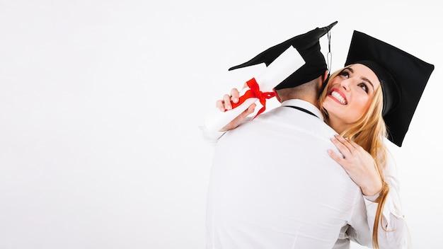 Abraçando homem e mulher com diplomas