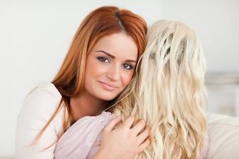 Abraçando jovens mulheres sentadas em um sofá