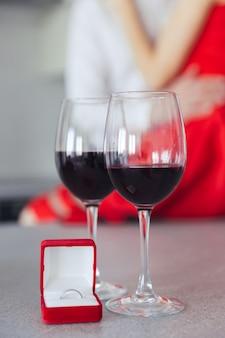 Abraçando lindo casal. copos com vinho e caixa com anel na mesa